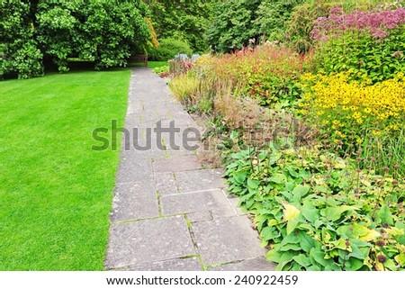 Stone Paved Pathway through a Beautiful Garden - stock photo