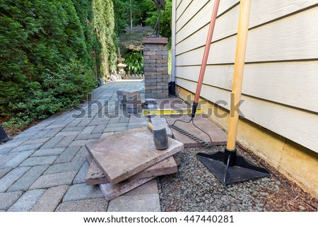 Stone Pavers and tiles for side yard patio hardscape for  garden landscaping tools rubber mallet sand gravel tamper level rake - stock photo