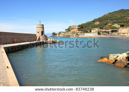 Stone pier with ancient tower and Recco shoreline in Liguria, northern Italy.