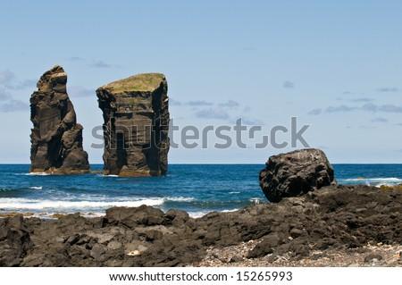 Stone pillars in the Atlantic Ocean. Massive natural monument made of lava stone. - stock photo