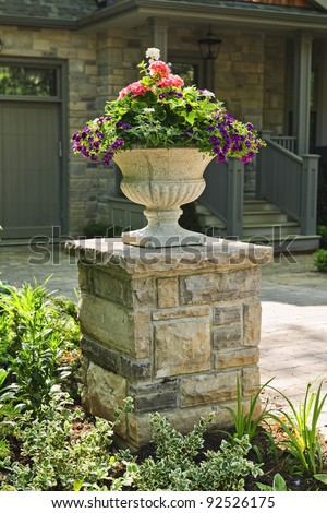 Stone planter with flowers near driveway of house - stock photo