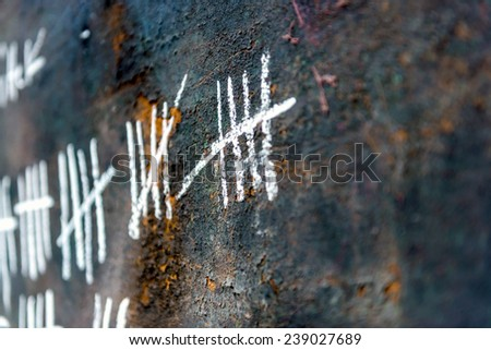 Stone prison wall and numbers close up - stock photo