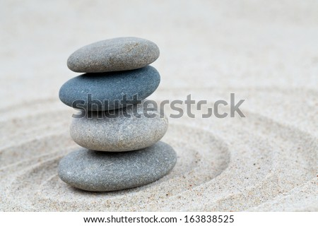 stone pyramid on sea sand - stock photo