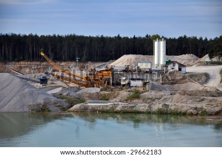 Stone quarry with silos, conveyor belts, and other mining equipment by the water - stock photo