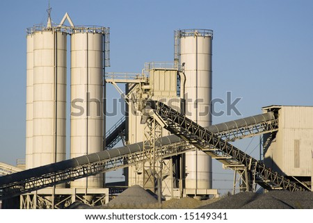Stone quarry with silos, conveyor belts, and piles of stones. - stock photo