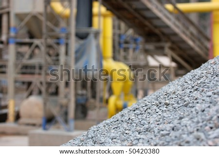 Stone quarry with silos, conveyor belts and piles of stones. - stock photo