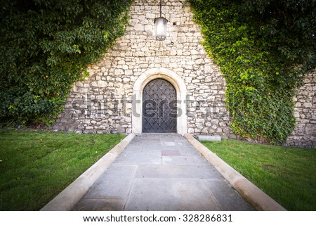 Stone road to old beautiful castle. Bright light from lamp in front of door, green grass and trees around. Beautiful landscape and interesting place for travel. - stock photo