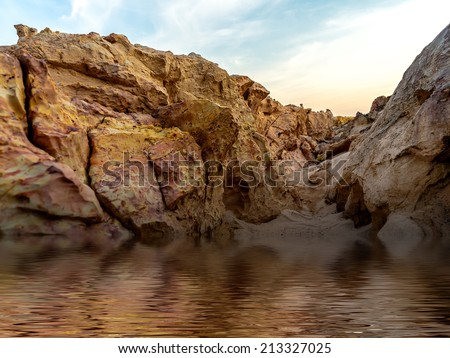 stone rock fills with water. digital compositing, colour tone, water reflection and ripple effects. - stock photo