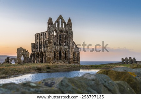 Stone ruins of Whitby Abbey on the cliffs of Whitby, North Yorkshire, England at sunset. - stock photo