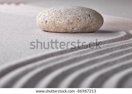 stone sand zen garden raked sand and pebble abstract for balance calmness spiritual and tranquil rippled pattern texture and lines background - stock photo
