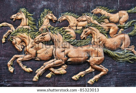 Stone sculpture of horse on wall in Thailand - stock photo