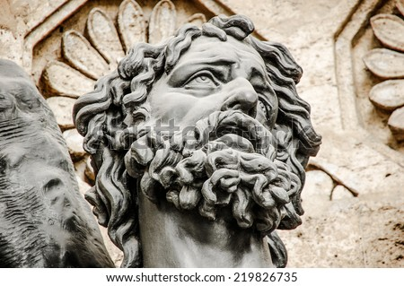 Stone sculpture showing head of man with curly hair. - stock photo