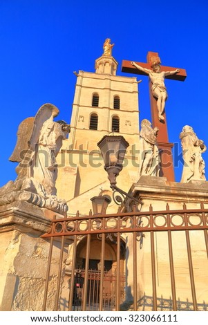 Stone sculptures and christian cross in front of the Avignon Cathedral, Provence, France - stock photo