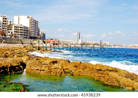 Stone seaside with hotels along on a sunny day in malta, blue water - stock photo