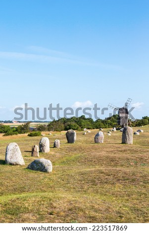 Stone ship on a meadow with a windmill - stock photo