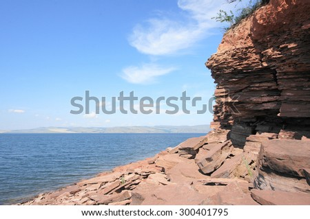 Stone shore of Krasnoyarsk reservoir on the river Yenisei. Sunny day, blue sky, clear water, red stones on the shoreline. Siberian nature landscape, Russia. July 25, 2015.