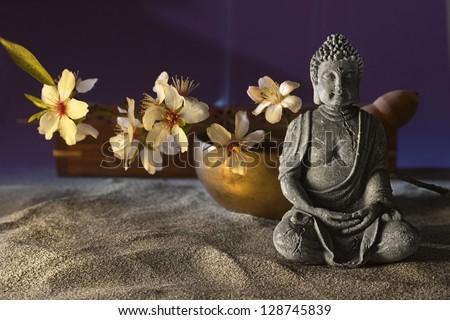stone sitting buddha flowers and  Tibetan bowl - stock photo