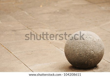 Stone sphere on the concrete tiled background - stock photo