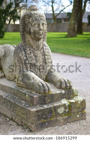 Stone sphinx sitting at the edge of a garden park - stock photo