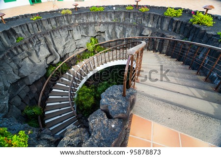 Stone spiral staircase with flowers in modern interior. - stock photo