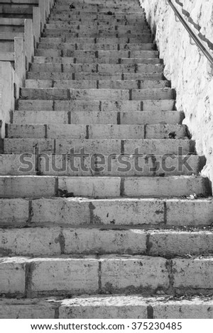 Stone stairs with metal hand rail. Jerusalem, (Israel). Black and white photo. - stock photo