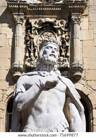 Stone statue of a man with a shield in the bottom out of focus - stock photo