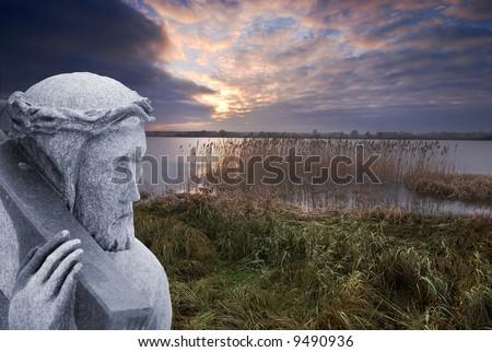 Stone statue of Jesus bearing the cross - stock photo