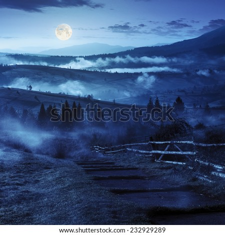 stone steps down the hill in to village in foggy mountains at night in full moon light - stock photo