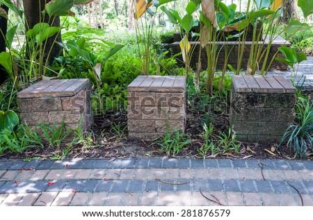 Stone stool in the small garden of urban park. - stock photo