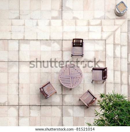 Stone terrace in the courtyard with a wooden table and chairs - stock photo