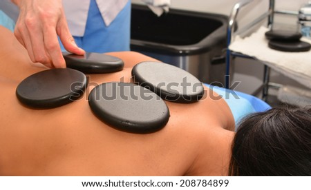 Stone therapy, stone massage, spa, woman doctor puts hot stones on the patient's back  - stock photo