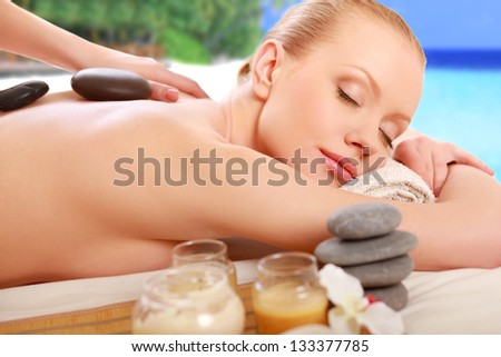 Stone therapy. Woman getting a hot stone massage