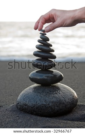 Stone tower build on a black beach. - stock photo