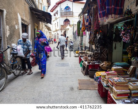 STONE TOWN, ZANZIBAR - MARCH 29, 2016: Local people walking on one of the streets in Stone Town, the capital of Zanzibar. Stone Town is famous for its colonial architecture.