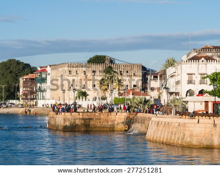 STONE TOWN, ZANZIBAR - MAY 02, 2015: Local people walking on the seafront in Stone Town, Zanzibar, Tanzania, East Africa and jumping to the water on the sunny evening. Horizontal orientation. - stock photo