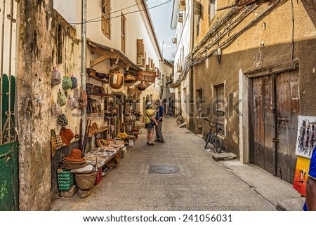 STONE TOWN, ZANZIBAR - OCTOBER 24, 2014: Tourists on a typical narrow street in Stone Town. Stone Town is the old part of Zanzibar City, the capital of Zanzibar, Tanzania. - stock photo