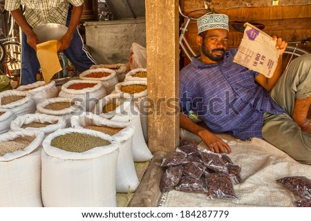 "STONE TOWN, ZANZIBAR/TANZANIA - APRIL 4 2012: Seller of Old Town Market, classic Swahili public space, mixing architectural and cultural influences. The heritage of Zanzibar market is the ""bazaar"". - stock photo"
