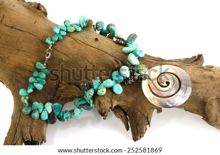 Stone, turquoise blue color drops his vocals arranged together into a necklace, a pearl fret wire from the top of the circle is beautifully placed on the timber, dry, brown on a white background.  - stock photo