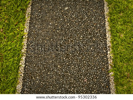 Stone walk path in old park with green grass background. - stock photo