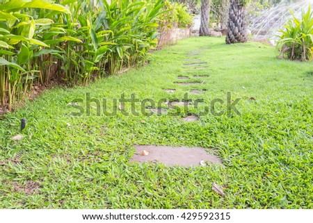 Stone walkway in the park which has Stucco as a wooden pole, Path through a Green Garden - stock photo