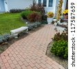 Stone walkway leading to driveway and footpath wth lush green grass lawn and flowerbed - stock photo