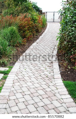Stone walkway on a grassy in the park - stock photo