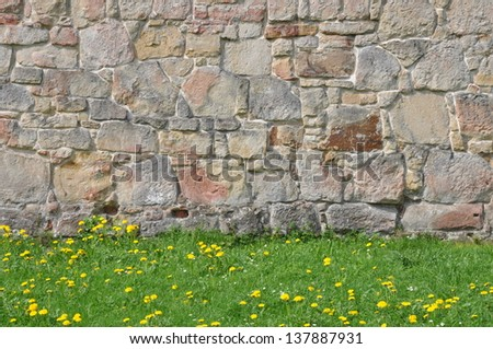 Stone wall and green grass - stock photo