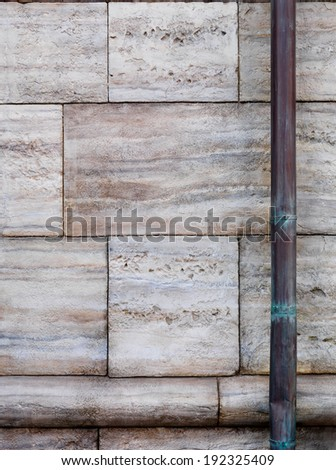 Stone wall and old copper downspout background texture - stock photo