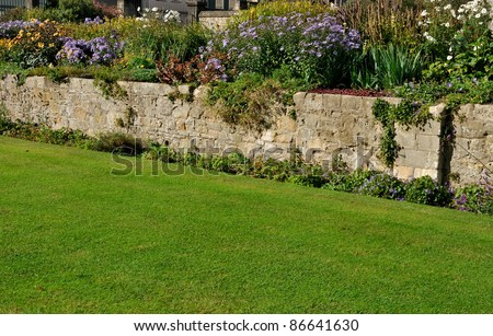 stone wall in traditional english garden - stock photo