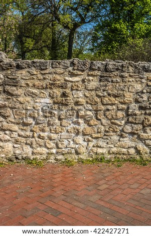 Stone wall masonry dividing forest and red paved sideway - stock photo