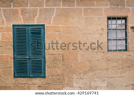 Stone wall of a house with two windows Two windows on the stone wall of an old house in the former capital of island Malta - Mdina. Closed green shutter, the other window without shutter. - stock photo