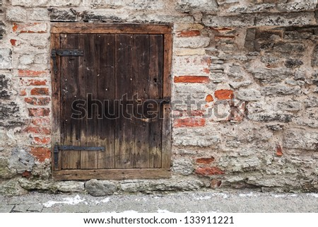 Stone wall of an ancient fortress with dark wooden door. Tallinn, Estonia - stock photo