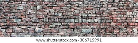 Stone wall panorama, panoramic stonewall pattern background, old aged weathered red grey grunge limestone dolomite slate slab rock texture, natural grungy, beige, yellow, gray brick vintage closeup - stock photo