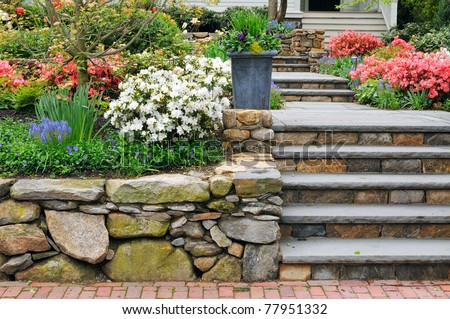 Stone wall, steps and planter on colorful landscaped garden - stock photo